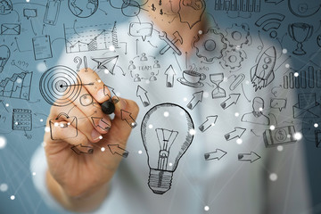 Businesswoman drawing a sketch lightbulb with a pen