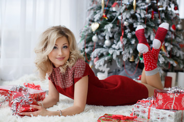 A chic woman,blue eyes, dressed in a red dress, spends Christmas Eve lying near a green elegant Christmas tree on a soft blanket, examining bright colorful boxes with Christmas gifts giving presents