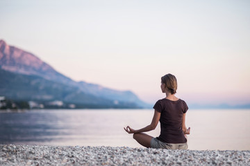 Young woman practicing yoga near the sea. Harmony and meditation concept. Healthy lifestyle