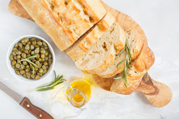 Fresh ciabatta with herbs and capers on a light background