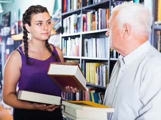 Old man with granddaughter are choosing books