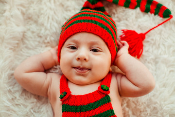 Charming little boy in long green and red hat lies on fluffy carpet