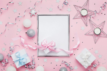 Christmas mockup with frame, holiday balls, gift boxes and sequins on stylish pink table top view. Fashion festive background. Flat lay.