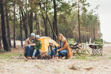 Tuinposter Kamperen family making campfire