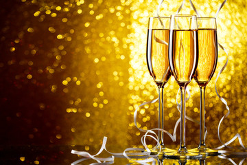 Three wine glasses with sparkling champagne with white ribbons on yellow background