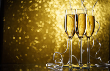 Picture of three glasses with champagne on gold background.