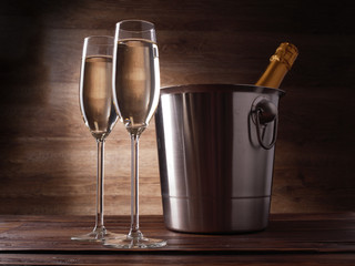Photo of two wine glasses with champagne, steel bucket