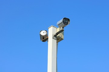 Two security cameras against blue sky background.