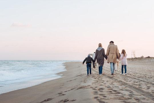 family walking on sandy beach