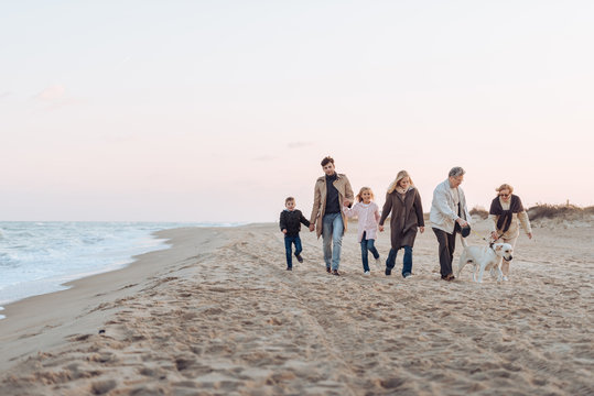 family walking with dog at seaside