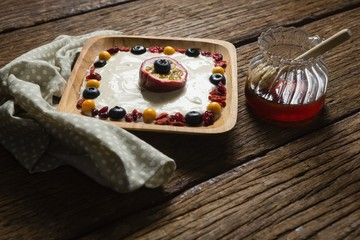 Fruit yogurt and honey on a wooden table