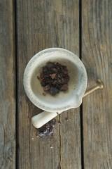 Black salt in mortar on wooden table