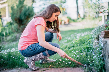 Young beautiful woman weeding in the garden with hoe