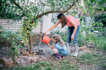 Mother and daughter watering a tree in the garden