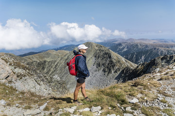 Happy hiker woman on the top of a mountain with stunning view .Musala peak in RIla mountain,Bulgaria