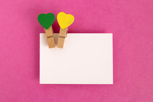 White sheet with green and yellow pins on the pink background for Valentine Day. Copy space.