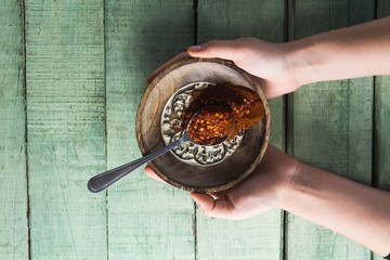 Hand holding chili powder and crushed red pepper in bowl