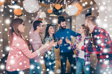 Happy cheerful student's team having party with champagne. Snowflakes background
