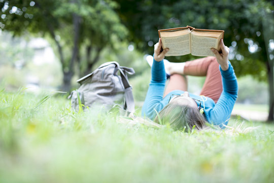 Young woman reading book at outdoor