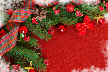 Happy New Year and Merry Christmas. New Year red background with spruce and decorations of balls and snowflakes.