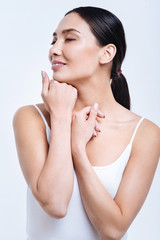 Pleasant woman closing her eyes while posing against white background