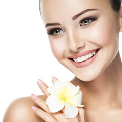 Beautiful smiling face of young woman with flower