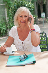 Smiling mature woman talking on smartphone and drinking coffee in the cafe.  Retired woman is chatting. Education for adults.