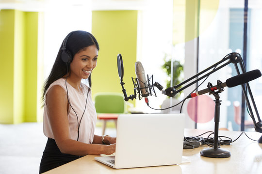 Young mixed race woman recording a podcast in a studio