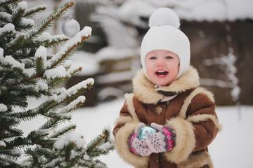 girl decorating christmas tree n the yard