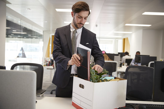 Fired male employee packing box of belongings in an office