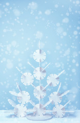 Stylized white christmas tree on a blue background, light bokeh with space for text