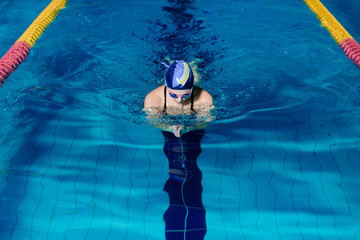 woman swimming with swimming hat in swimming pool