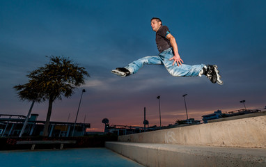 inline skater man jumps in the street