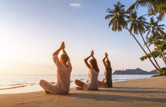 People practicing yoga on the beach, wellbeing, warm tropical landscape