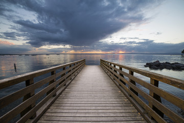 wooden pier on the sea in front of a fiery sunset