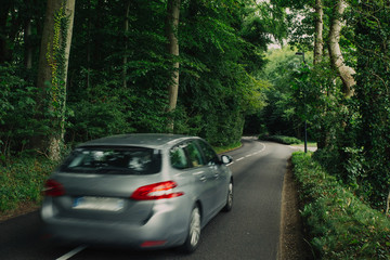 Cars driving on the asphalt road passing through the green forest in the region of Normandy, France. Nature, countryside landscape, transportation and road network concept