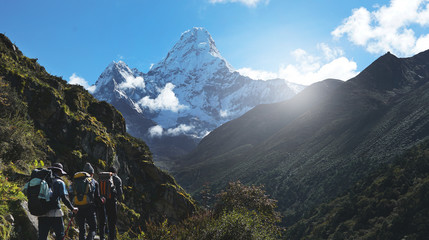 Three Trekkers Walking on Everest Highway While Seeing Mount Ama Dablam, Everest Base Camp Trek From Tengboche to Dingboche , Nepal