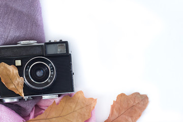 Old camera and autumn leaveson a white background .
