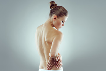 Studio portrait of young woman with naked torso touching painful back.
