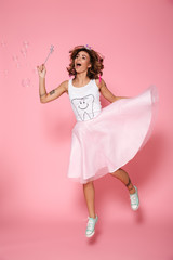 Full length portrait of happy young brunette woman dressed like fairy holding magic wand, looking aside while jumping over pink background
