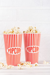Popcorn vertical banner. Red stripped paper cup and kernels staying on white wooden background. Copy space.