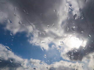 Splashes of rain on the glass / Stormy rain clouds in blue sky, splashes of rain on the glass