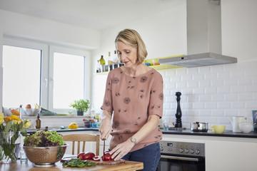 Mature woman preparing a salad in kitchen