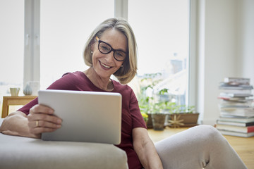Smiling mature woman at home using tablet on the sofa