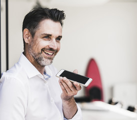 Happy businessman using cell phone in office