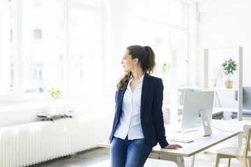 Businesswoman leaning on desk looking out of window