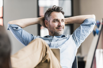 Businessman in office leaning back