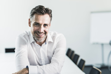 Portrait of smiling businessman in conference room
