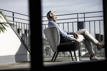 Grey-haired man relaxing in chair on balcony listening to music