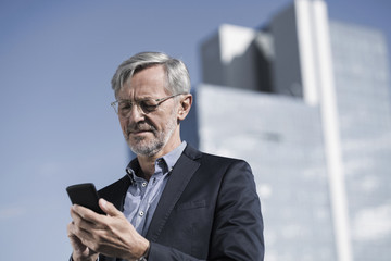Grey-haired businessman typing into smartphone